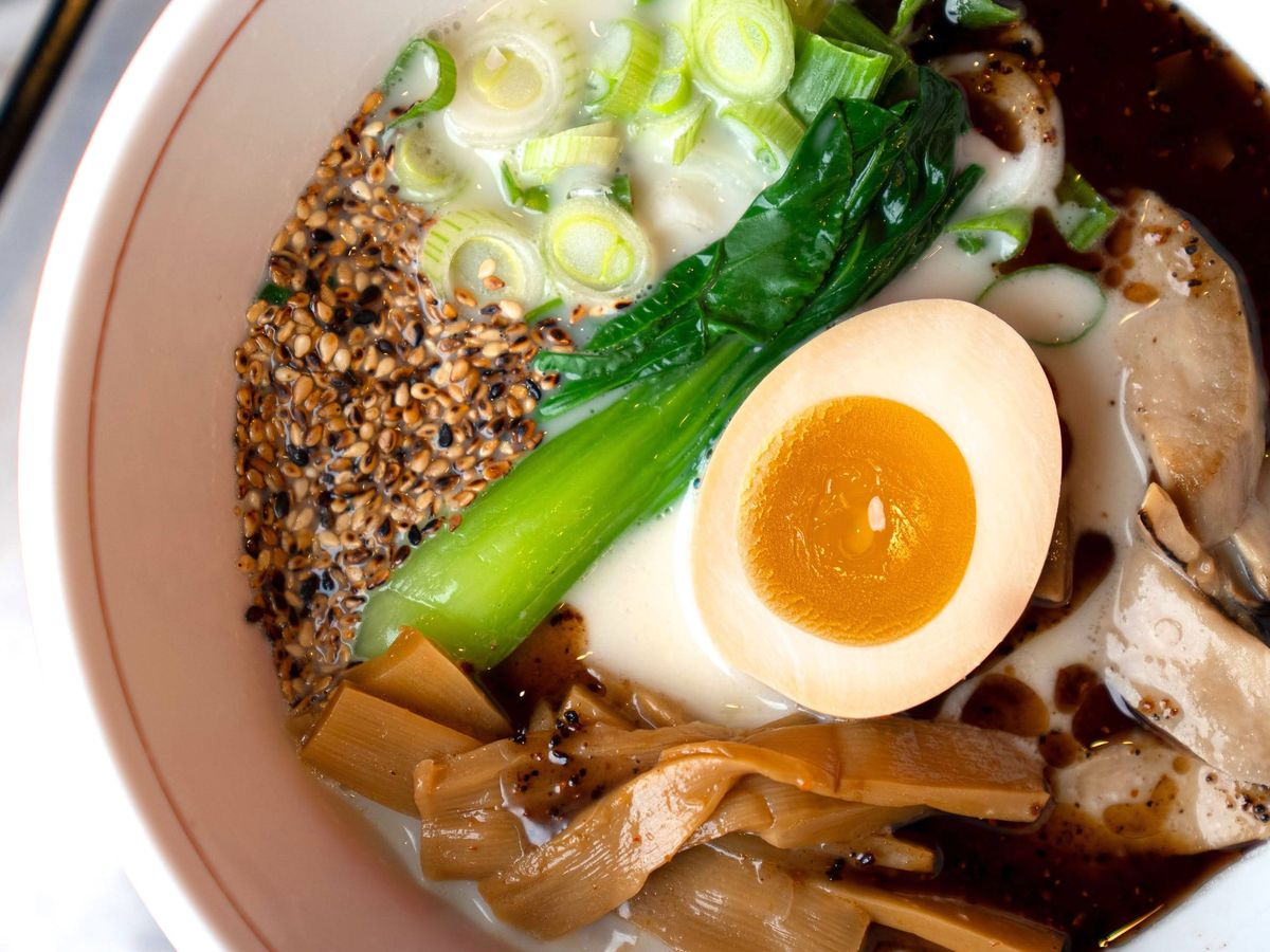 A bowl of ramen with especially milky broth, hard boiled egg, scallion, slices of meat, seeds, bok choy, and burdock root