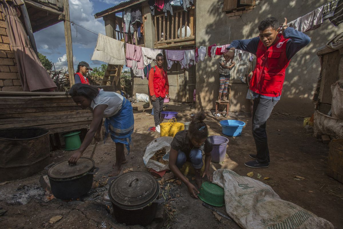 Red Cross volunteers speak to women as they are busy cooking, whilst educating villagers about the plague outbreak, 30 miles west of Antananarivo, Madagascar, Monday, Oct. 16, 2017. As plague cases rose last week in Madagascar's capital, many city dwellers panicked. They waited in long lines for antibiotics at pharmacies and reached through bus windows to buy masks from street vendors. Schools have been canceled, and public gatherings are banned. (AP Photo/Alexander Joe)