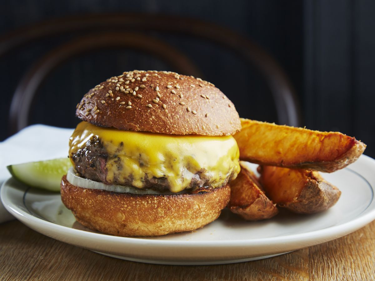 Dry-aged burger with American cheese, onions, and wedge fries at Red Hook Tavern