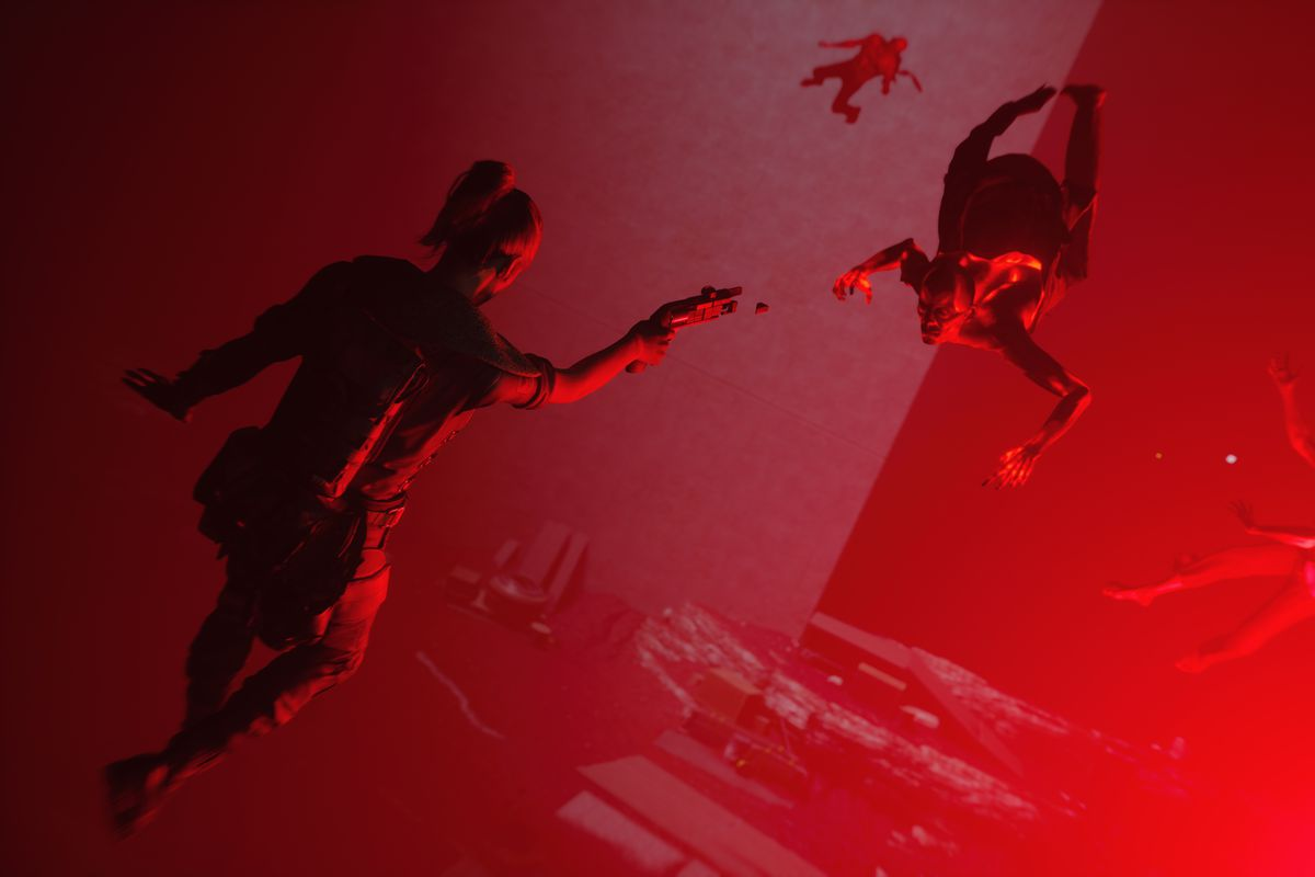 a woman floating in the air in a red room aims a gun at a monster in Control