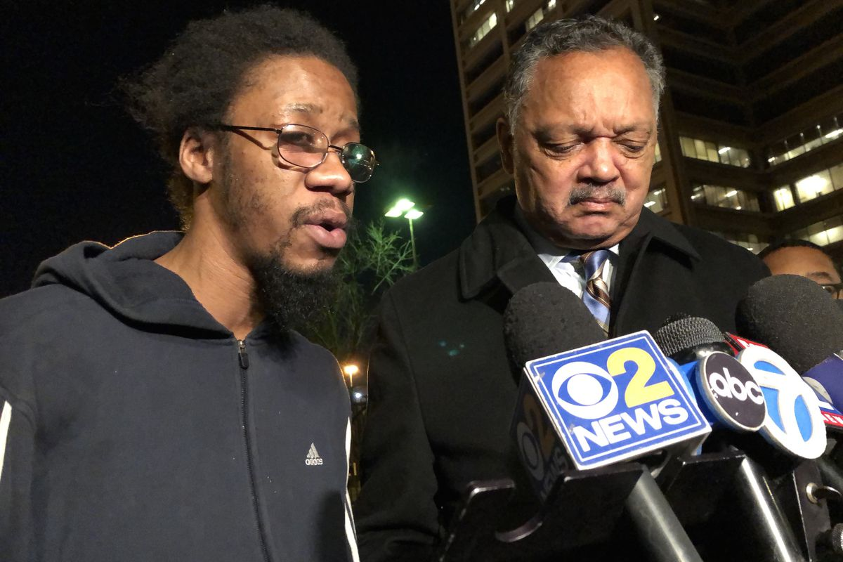 Bernard Kersh stands beside the Rev. Jesse Jackson Jr. to address reporters as he left the Cook County Jail in December following his arrest for allegedly spitting on a Chicago Police officer, who then body slammed the 29-year-old, who has a history of mental illness.
