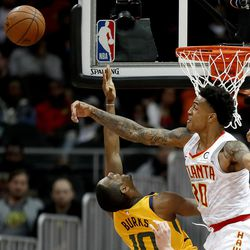 Atlanta Hawks' John Collins, right, blocks the shot of Utah Jazz's Alec Burks in the fourth quarter of an NBA basketball game in Atlanta, Monday, Jan. 22, 2018. (AP Photo/David Goldman)