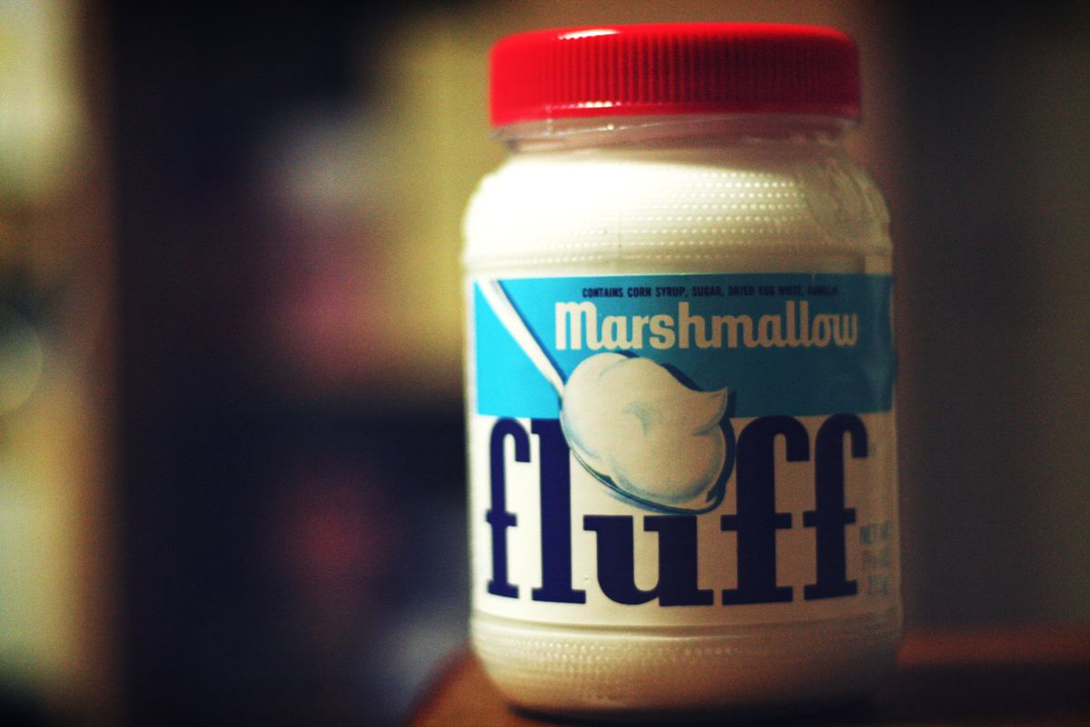 Product shot of a jar of marshmallow Fluff with a red cap and a light blue and white label with dark blue lettering. The jar appears in front of a dark, blurred background.