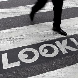 """A pedestrian walks past a """"Look!"""" sign on the crosswalk at the intersection of 42nd St. and 2nd Ave. in New York, Thursday, Sept. 20, 2012.  Crossing the street in New York City is complicated: Even when it's one-way, you should look both ways, and stop texting for a few seconds.  That's what city transportation officials tell pedestrians who often miss getting hit in the chaotic every-which-way-including-loose mill of vehicles, bicycles, scooters and sometimes, carriage horses.  They're making their point visible with """"LOOK!"""" signs stenciled at 110 of the most dangerous intersections in the city's five boroughs."""