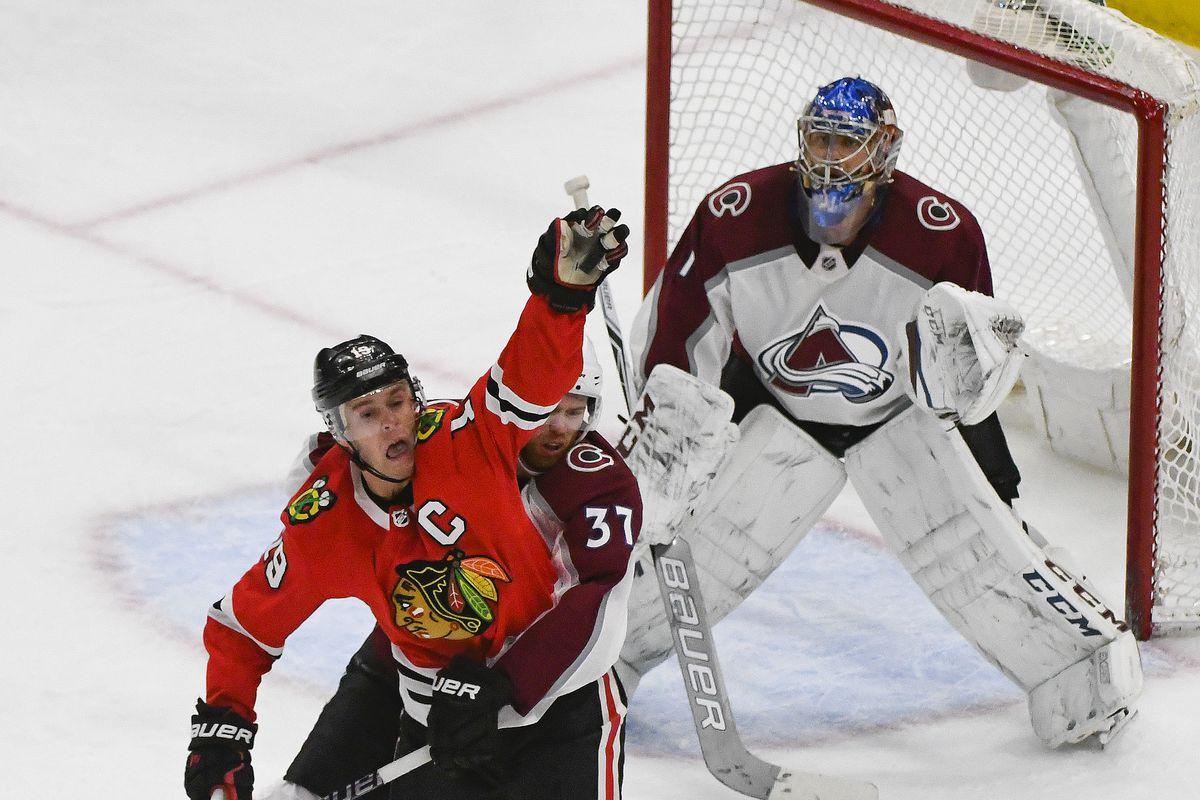 332a9659963 ... Jonathan Toews (19) catches a puck then drops it as Colorado Avalanche  left wing J.T. Compher (37) and Colorado Avalanche goaltender Semyon  Varlamov (1) ...