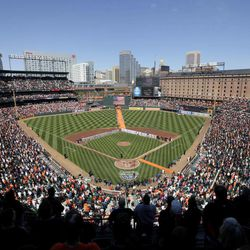 Fans and players stand for the national anthem before the Baltimore Orioles' home opener baseball game against the Minnesota Twins in Baltimore, Friday, April 6, 2012.