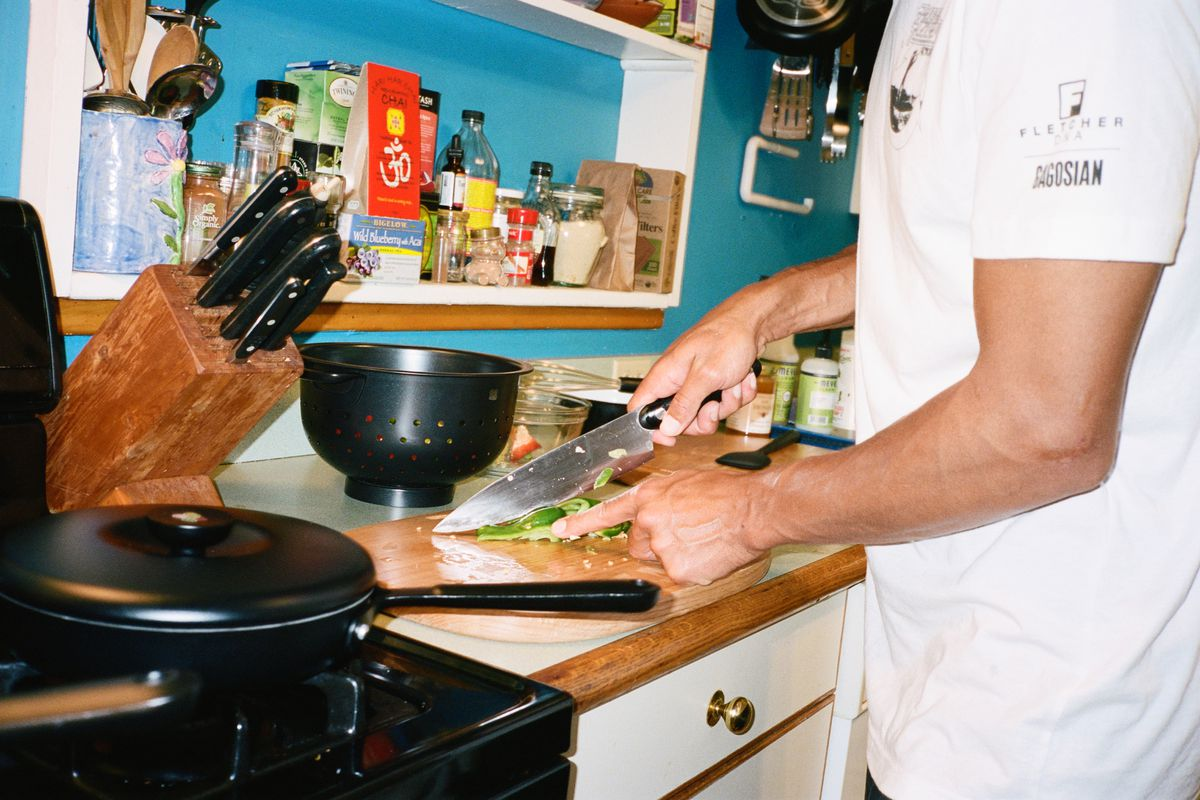 Man chopping vegetables on wooden board. A black pot and prep bowl sit nearby.