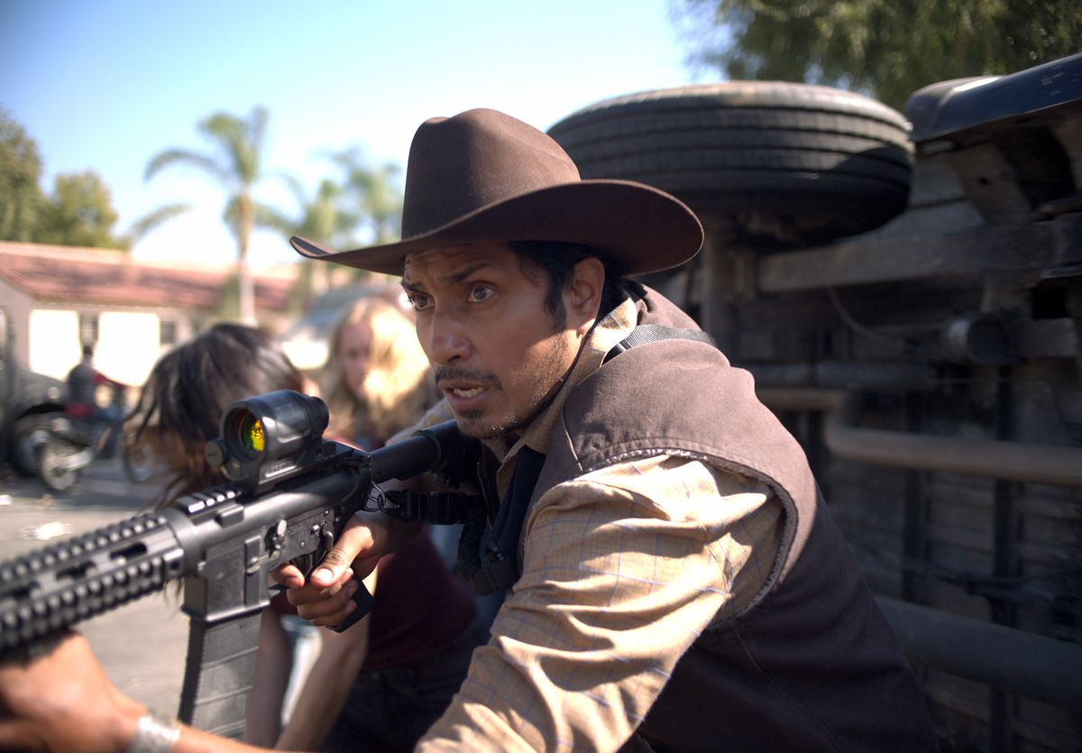 Tenoch Huerta as Juan, holding an assault rifle at ready in The Forever Purge
