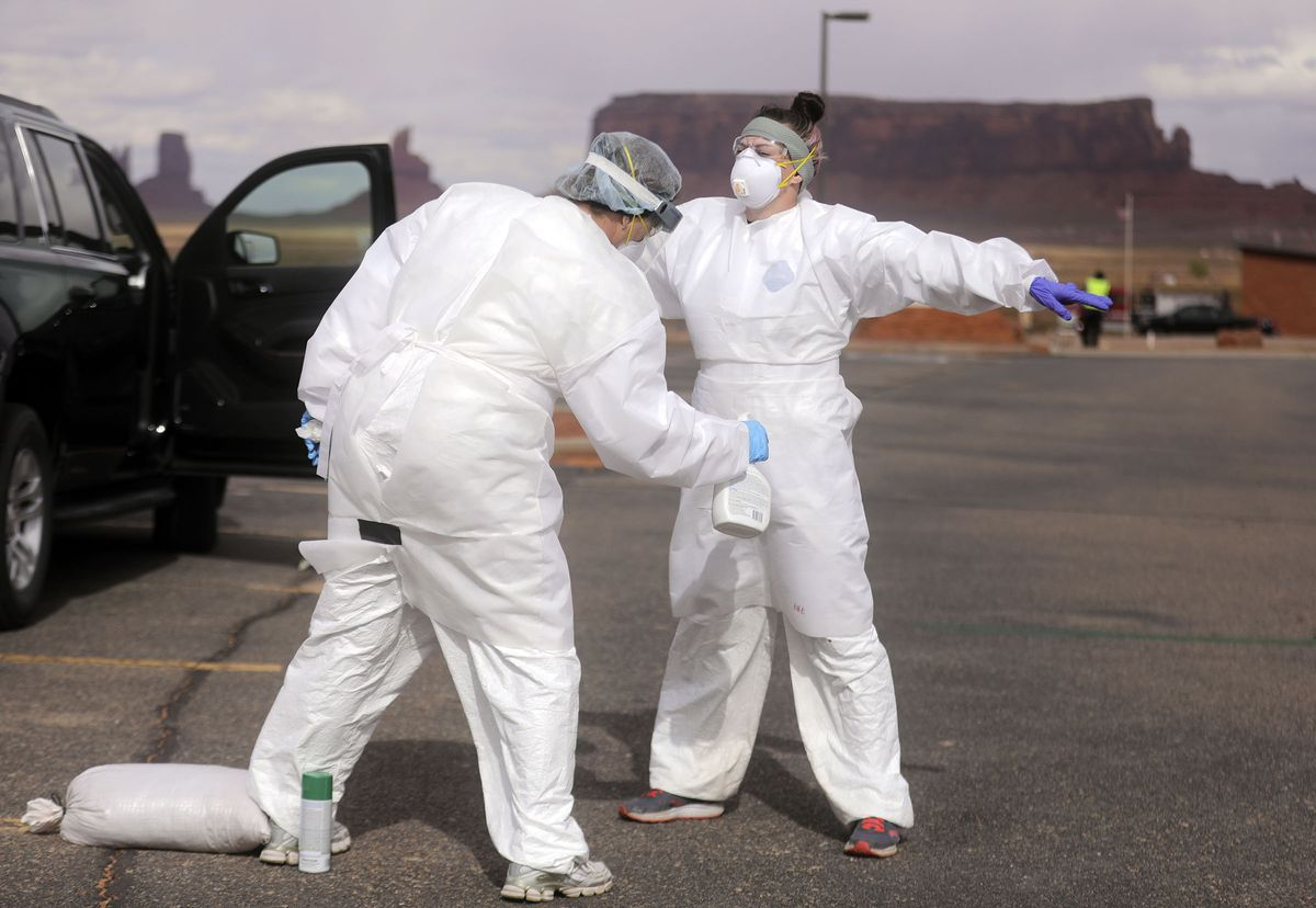 Kelly Carnahan, Utah Public Laboratory emergency manager, sprays down her daughter, Cassidy Scott, who provides administrative support, after they finished a day of COVID-19 testing outside of the Monument Valley Health Center in Oljato-Monument Valley, San Juan County, on Thursday, April 16, 2020. The mobile testing team tested 1,060 people in two days.