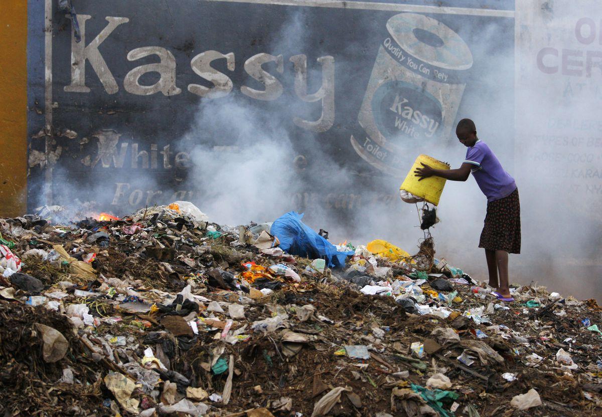 A Kenyan empties her can onto a huge pile of smoldering garbage in the Kibera slums in 2008 in Nairobi, Kenya.