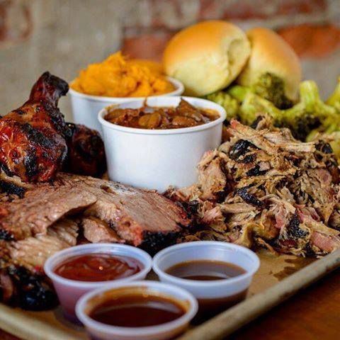 barbecue meat on a tray with containers of sauces and sides