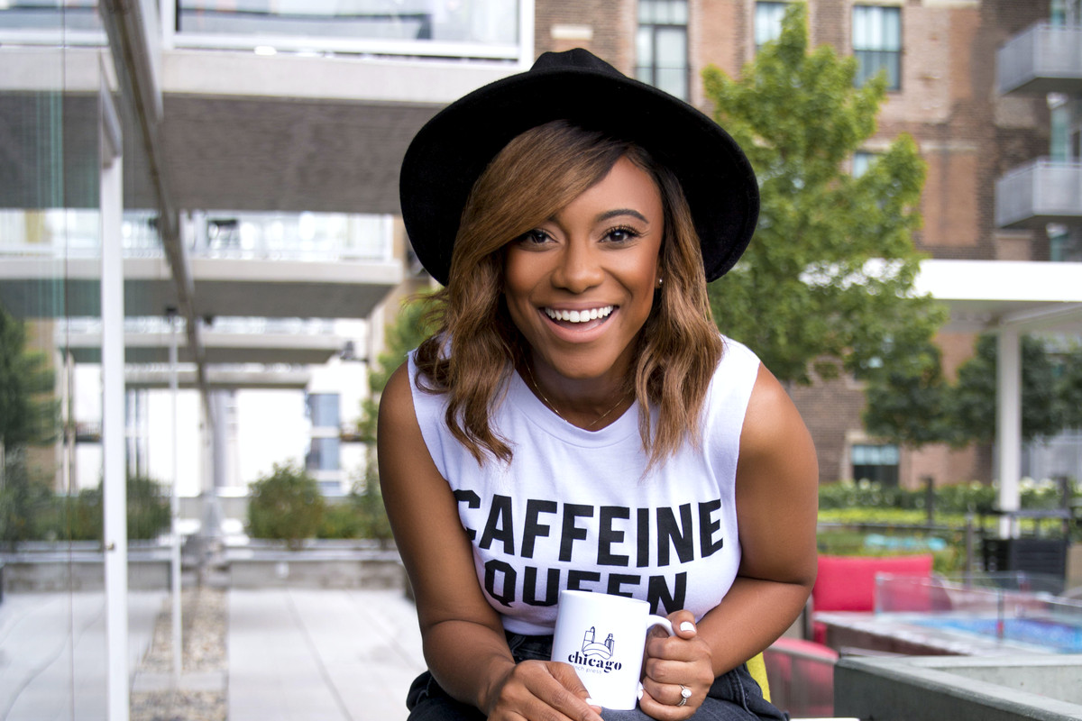 A person smiling, wearing a black rimmed hat, holding a coffee cup while sitting on a stool.
