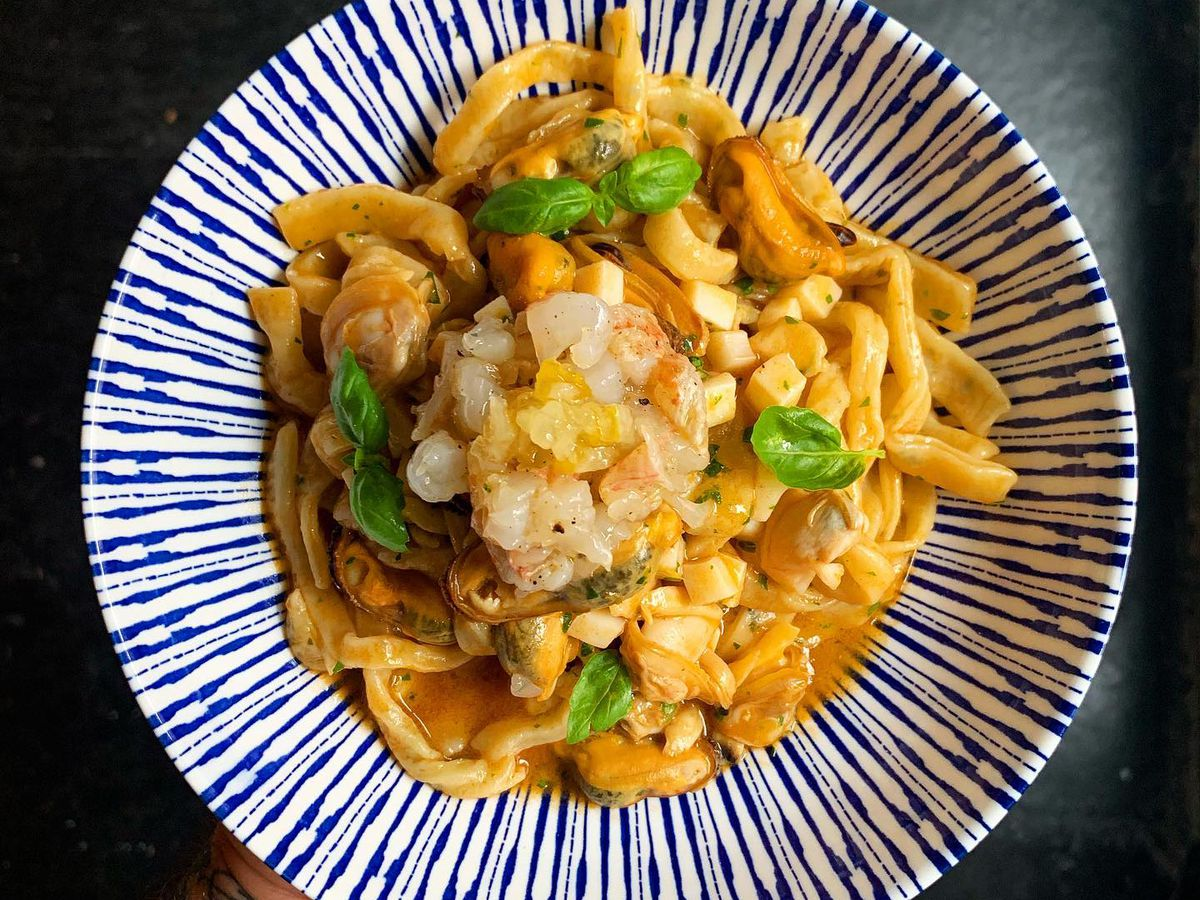 From above, a hand holding a geometric plate piled with scialatielli pasta topped with a mound of chopped seafood and a few scraps of herbs