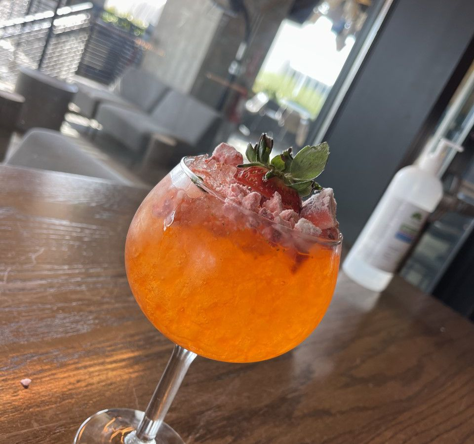 An orange cocktail in a wine glass has freeze dried berries and a strawberry on the rim