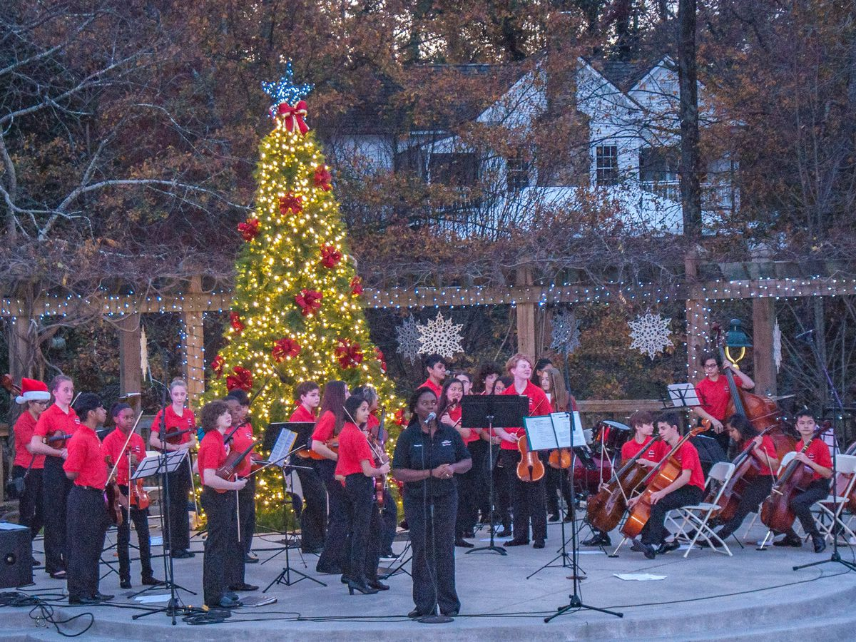 People playing musical instruments stand in front of a Christmas tree which is illuminated with many lights at Sparkle Sandy Springs.