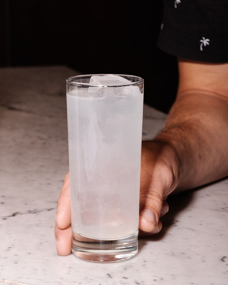 A tall glass with an opaque drink on a bar with a hand holding it at its base