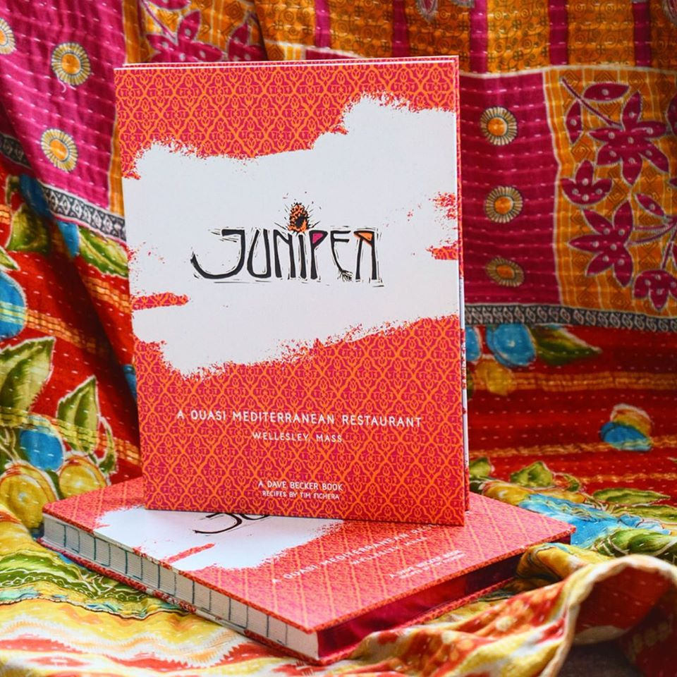 Two copies of a cookbook with a bold red cover are displayed — one laying flat and the other standing up on top of the first — on a piece of colorful, floral fabric.