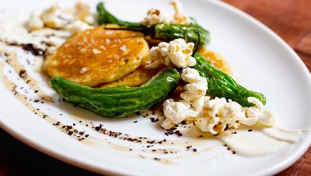 A plate of small yellowish-brown pancakes, embellished with shishitos, popcorn, and urfa