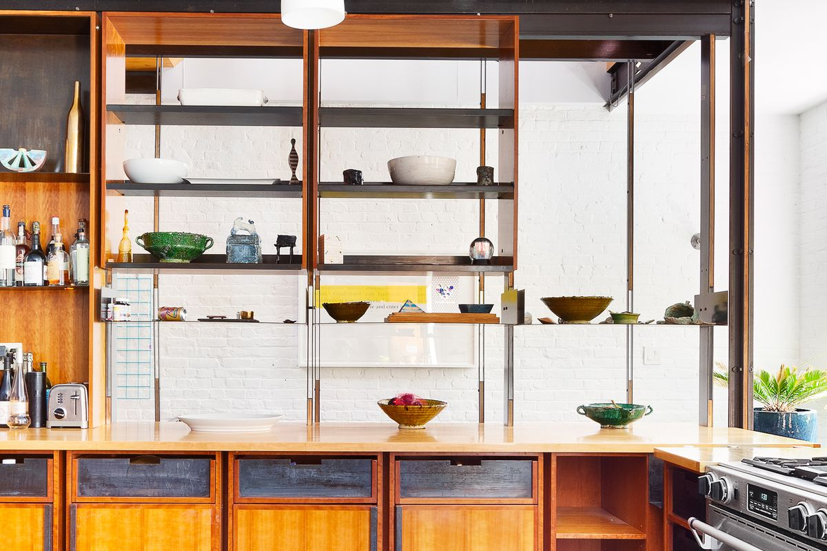 A kitchen with wooden shelves and counters.