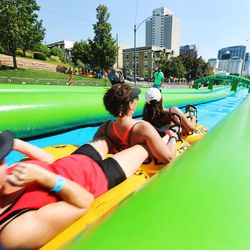 Hundreds enjoy the sun and water Saturday, Aug. 22, 2015, as they participate in Slide the City, in Salt Lake City.