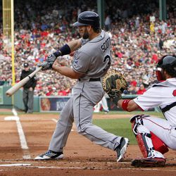 Tampa Bay Rays' Luke Scott, left, hits a three-run home run in front of Boston Red Sox's Jarrod Saltalamacchia (39) in the first inning of a baseball game in Boston, Saturday, April 14, 2012.