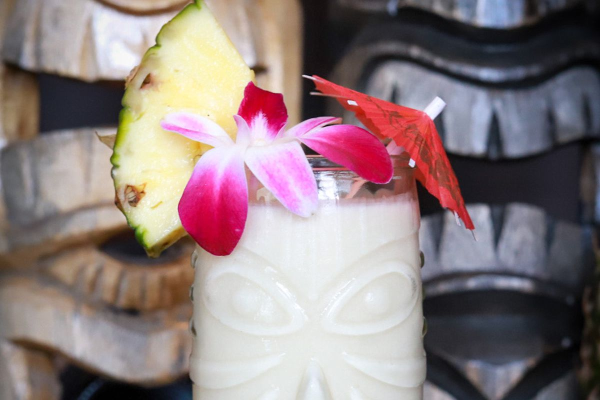 A pina colada decorated with orchids in a clear tiki mug.