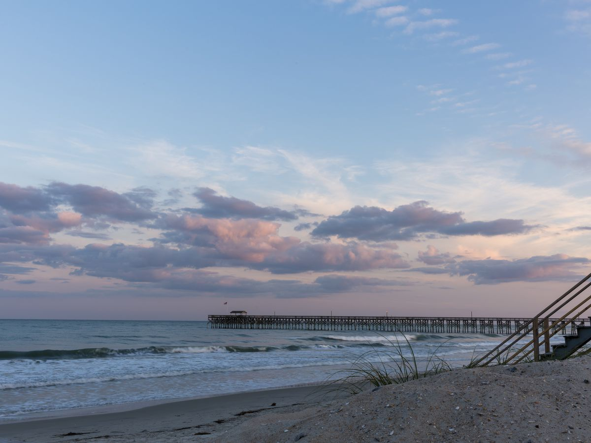 In the foreground is a sandy beach. In the distance is the ocean. It is sunset and the sky is purple, pink, and blue.