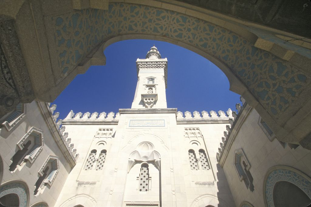 The facade of a mosque seen from below. At the top is a tower.