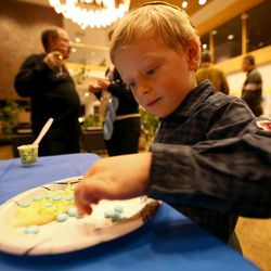 Joshua Kaplan decorates a cookie for his grandmother at the annual Hanukkah party at Temple Har Shalom in Park City on Saturday, Dec. 13, 2014.