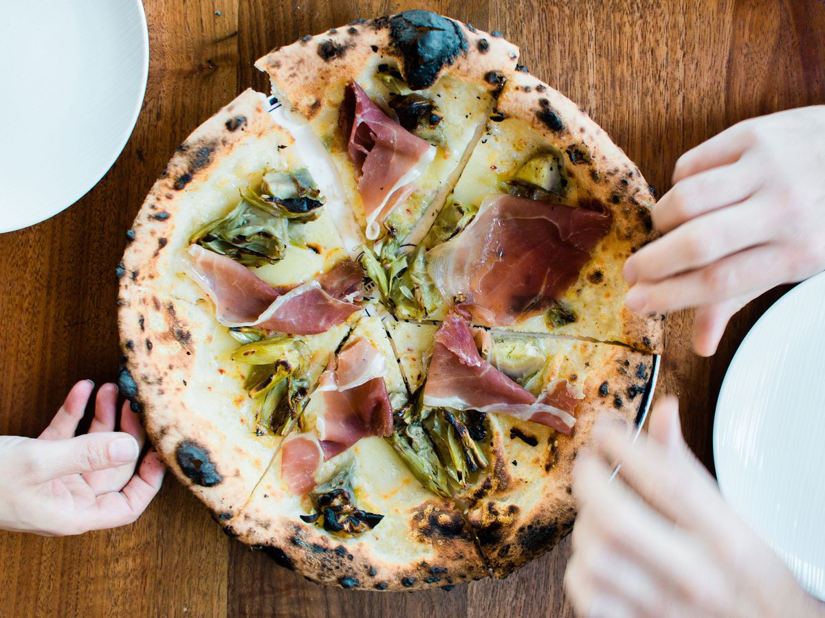 People sharing a pizza at Catania restaurant in La Jolla