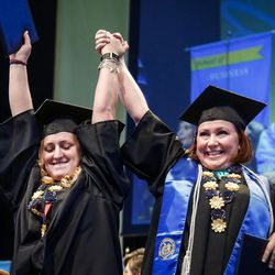 Salt Lake Community College graduates hold their hands up in triumph after receiving their diplomas during the 2017 commencement ceremony at the Maverik Center in West Valley City on Friday, May 5, 2017.