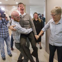 Derek Kitchen picks up Laurie Wood as Amendment 3 case plaintiffs leave their press conference Monday, Oct. 6, 2014, in the office of Peggy Tomsic in Salt Lake City, after the U.S. Supreme Court refused to hear appeals on lower court rulings that allowed same-sex marriages, making them legal in Utah and other states.