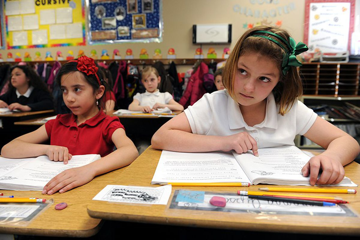 Natalia Lima Avalos, 8, left and Esperanza Gipson, 8, listen closely during their fourth grade writing class at James Irwin Charter Elementary school in Colorado Springs. (Helen H. Richardson, The Denver Post)