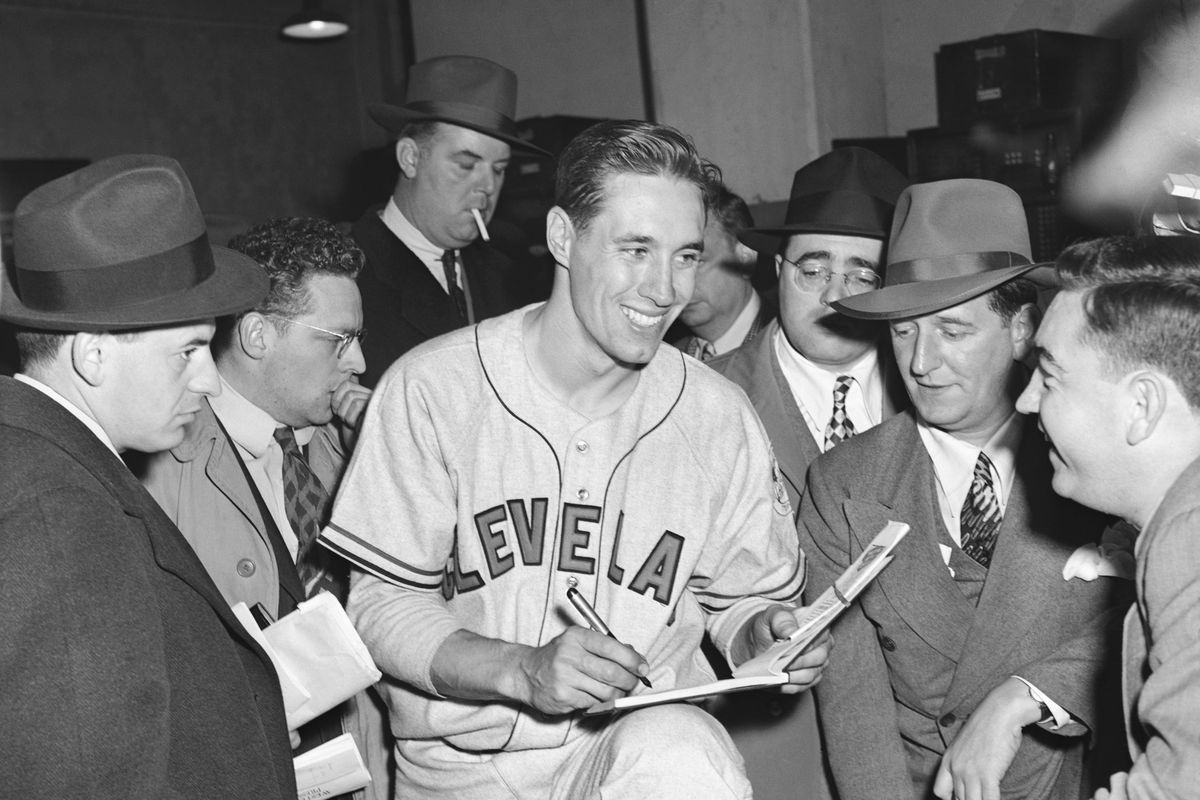 Bob Feller signs autographs for reports, 1945