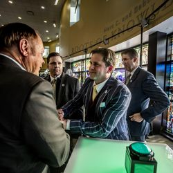 """Marc Bingham, from left, shakes hand with Tom Holdman as Cameron Oscarson and Utah Valley University president Matthew S. Holland look on after the unveiling of the """"Roots of Knowledge"""" in the Fulton Library on the UVU campus in Orem on Friday, Nov. 18, 2016."""