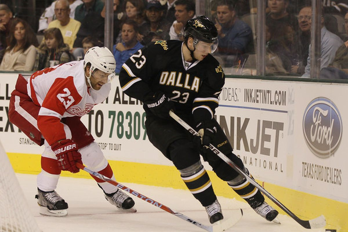 DALLAS - OCTOBER 14: Tom Wandell #23 of the Dallas Stars takes the puck as Brad Stuart #23 of the Detroit Red Wings defends on October 14 2010 at the American Airlines Center in Dallas Texas.  (Photo by Elsa/Getty Images)