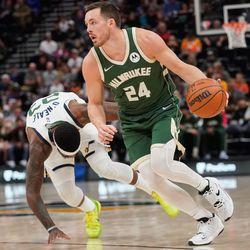 Milwaukee Bucks guard Pat Connaughton runs past Utah Jazz forward Royce O'Neale during an NBA preseason game at Vivint Arena in Salt Lake City on Wednesday, Oct. 13, 2021.