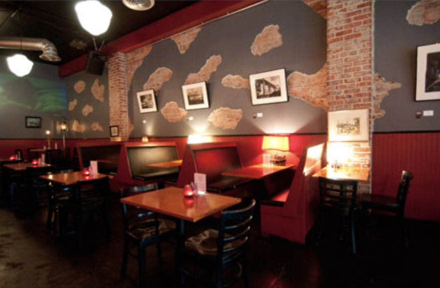The low-lit interior of Gainsbourg with red booths and clouds painted on the walls.