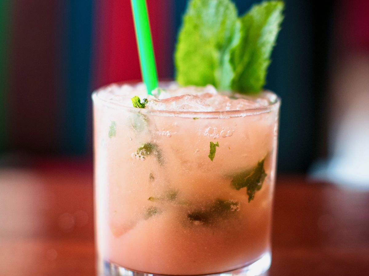 pink cocktail with leaf garnish and green straw