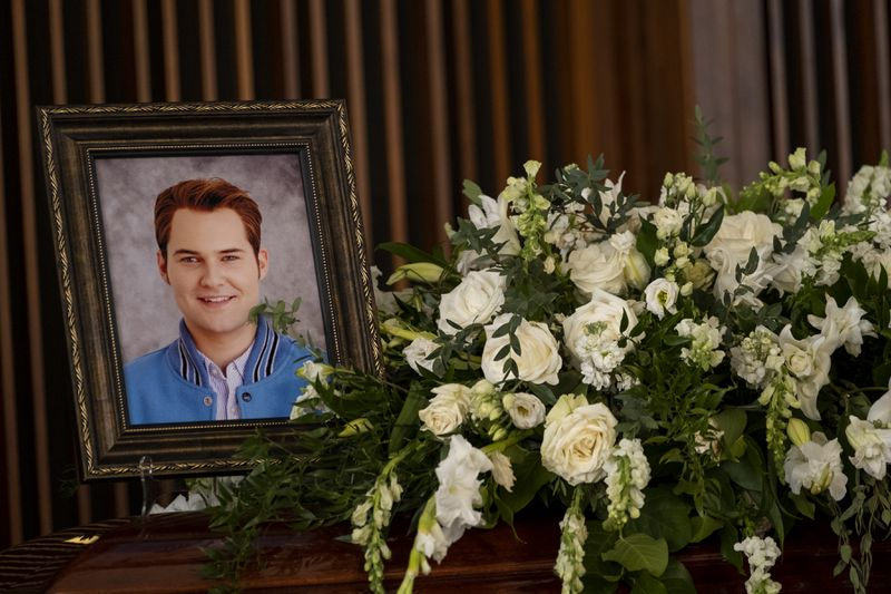 A photo of Bryce (Justin Prentice) next to a coffin and flower arrangement