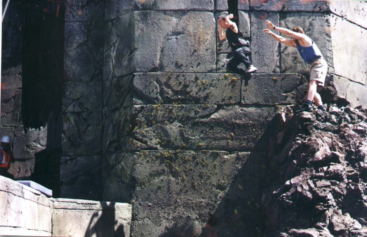 """A man in shorts and a blue tank top """"hurls"""" actor Brett Beattie from a rocky outcropping on the set of Helm's Deep. Beattie hangs in midair, aiming for a safety pad a dozen feet away and down across a huge gap."""