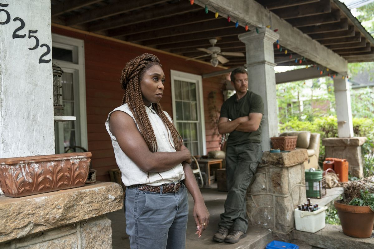 Cynthia Erivo and Max Beesley stand on the junk-covered front porch of a run-down house, looking dubiously at something offscreen.