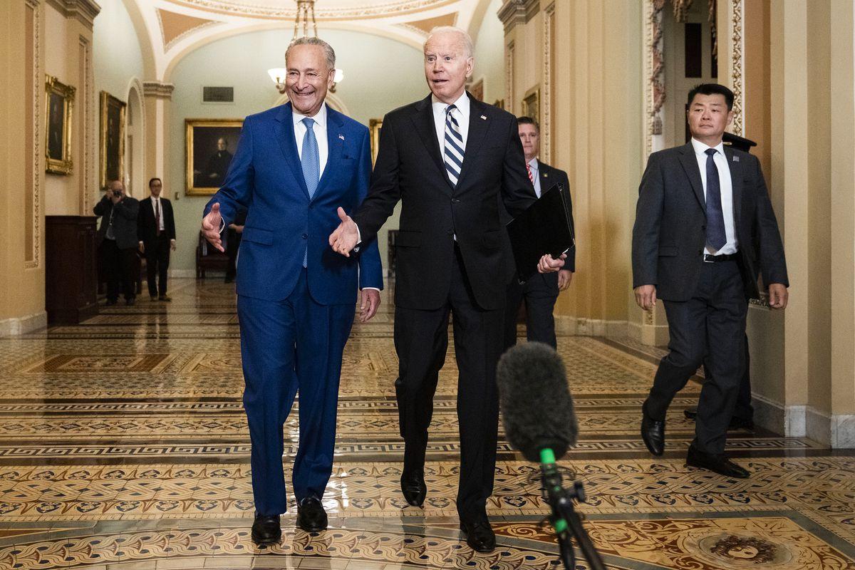 Senate Majority Leader Chuck Schumer and President Joe Biden walking together in the US Capitol building.