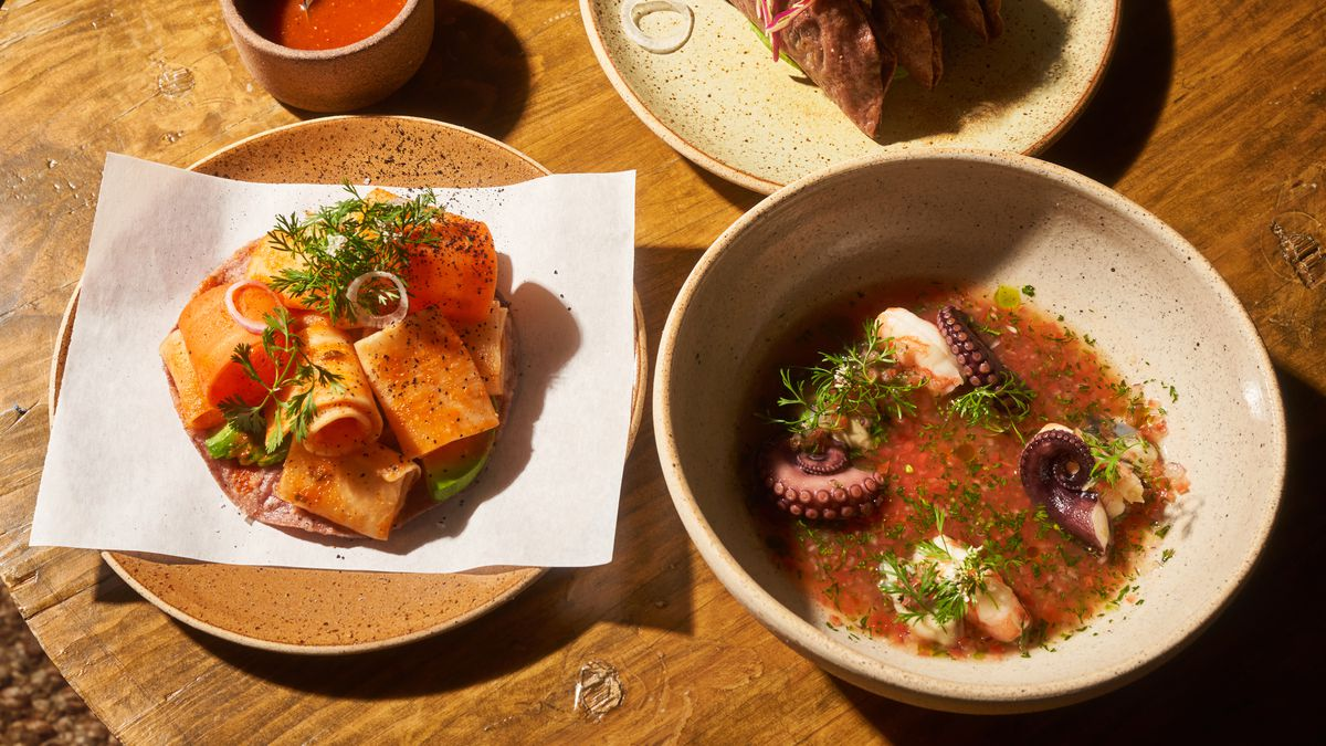 Three dishes, including a daikon tostada, a ceviche with octopus, and tacos, are arranged on a wooden table
