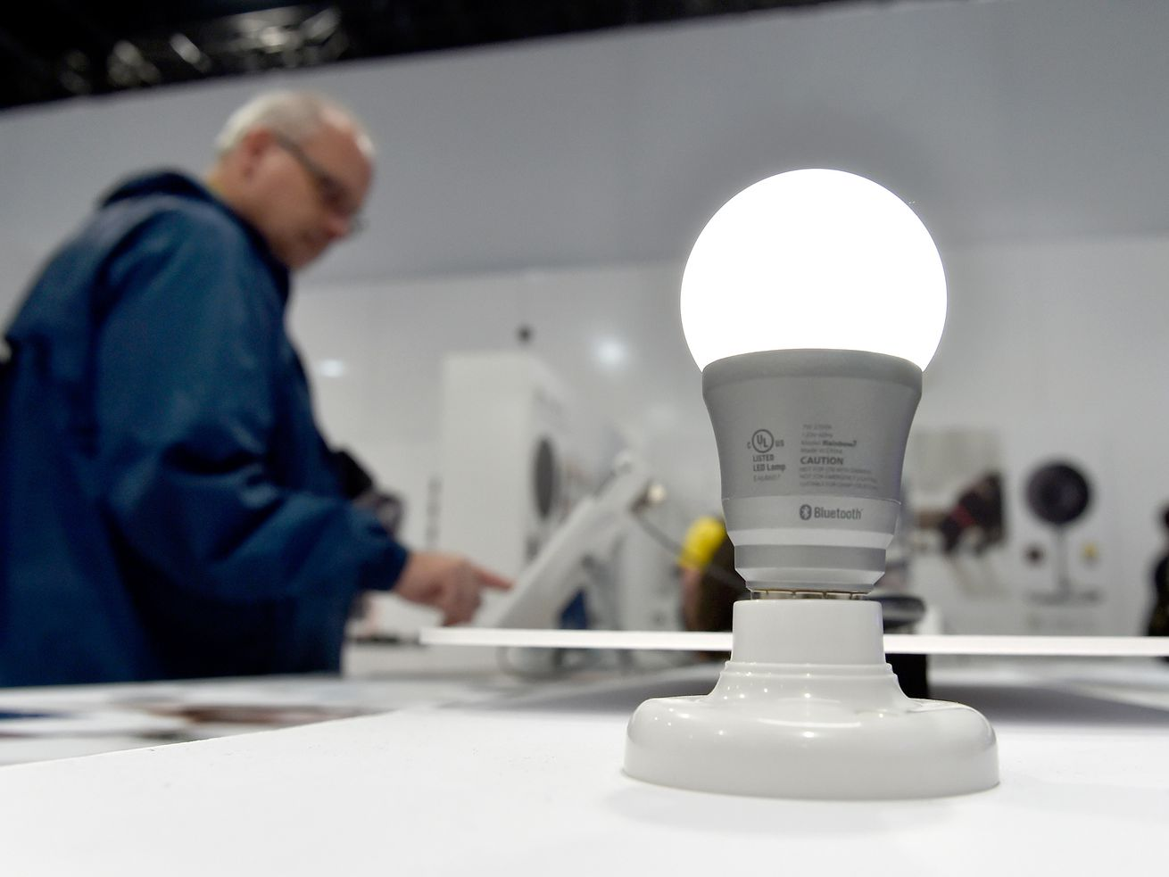 A high-tech, energy-efficient LED light bulb is seen on a display at CES, the consumer electronics show, with a man browsing the booth in the background.
