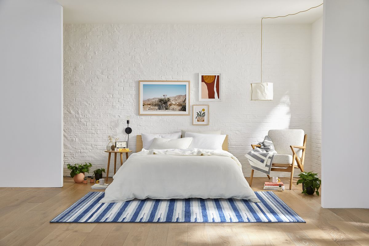Bedroom with white duvet and blue patterned rug.