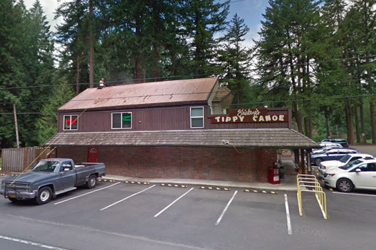"""A brown, wood-paneled restaurant sits on a summery day with a few cars in its small wraparound parking lot. A sign reading """"Shirley's Tippy Canoe"""" sticks up from the restaurant's awning."""