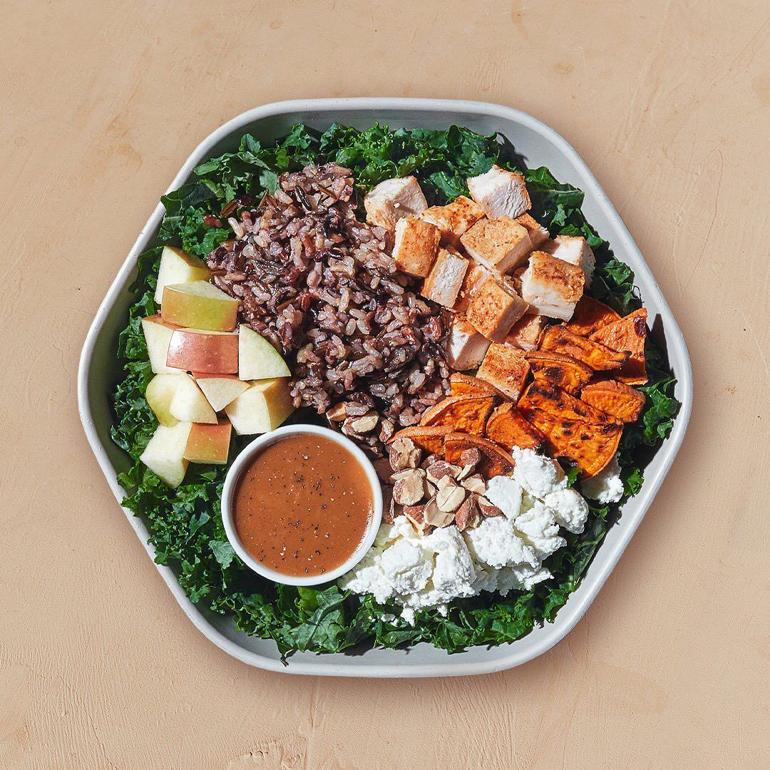 Hexagon tin bowl containing red rice, sliced apples, cauliflowers, cubed grilled chicken on a bed of kale greens