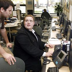 """David """"Sparky"""" Mortimer, seated, confers with his sports editor at BYU's Daily Universe."""