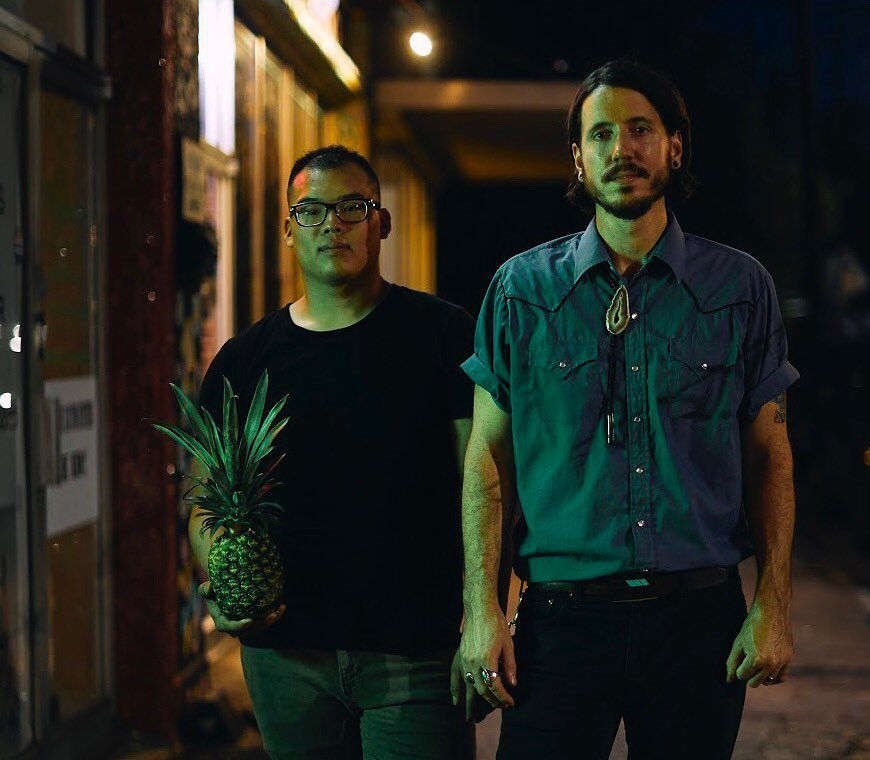 Chefs Parnass Lim Savang and Rod Lassiter standing outside on the sidewalk at night holding a pineapple